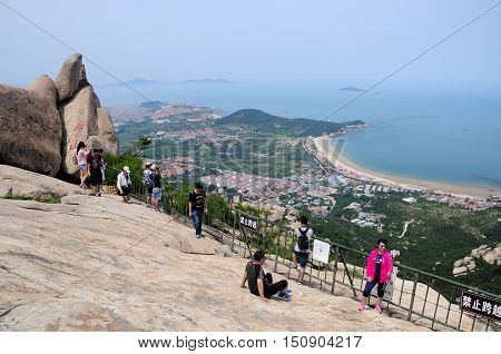 June 26 2016. Qingdao China. Chinese tourists on the summit of Laoshan (mount Lao) in Qingdao China in Shandong province with the East Sea and coastal city in the background.