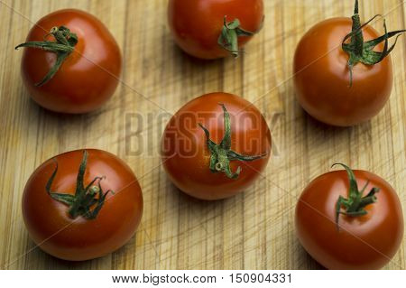 Red delicious tomatos on a wooden table