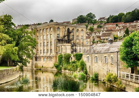 Exterior of old mill building on River Avon in Bradford on Avon, Wiltshire, England on sunny day.