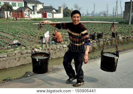 Pengzhou, China - January 24, 2010: Farmer carrying two pails of water suspended from a shoulder yokes walking along a country road.