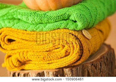knitted green and orange sweater on a tree stump