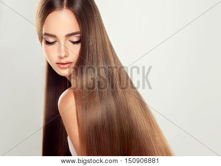 Beautiful model woman with long, straight, healthy and shiny black hair.