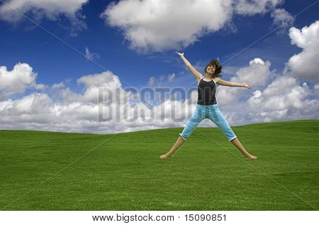 Beautiful happy woman jumping on a green field