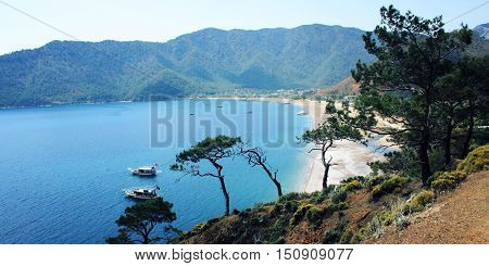 Tourist boats in the sea. View on Adrasan Bay. Aged photo. Pine trees and sea. Toned image. Walking the Turkey's Lycian Way. Antalya Province Turkey. Wide format for a slider.