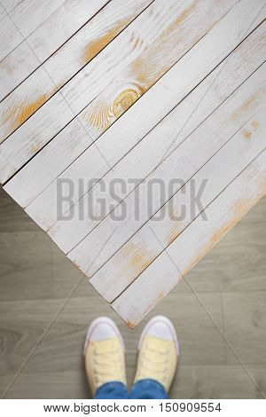 Foot and legs seen from above with vintage white wooden table top view. Empty space.