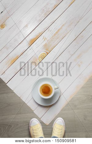 Foot seen from above with vintage white wooden table and coffee top view. Empty space.