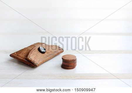 little old retro purse and a stack of coins on a light wooden background / small beginning of big business