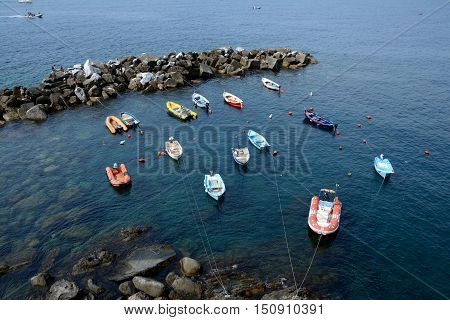 Riomaggiore Italy - September 4 2016: Boats in small harbour in Riomaggiore city in Liguria Italy. One of five Cinque Terre cities (unesco world heritage). Unidentified people visible.