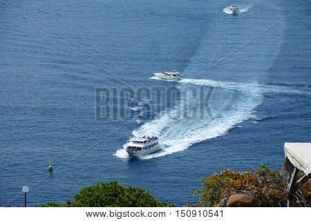 Riomaggiore Italy - September 4 2016: Passenger boats nearby Riomaggiore city in Liguria Italy. One of five Cinque Terre cities (unesco world heritage). Unidentified people visible.