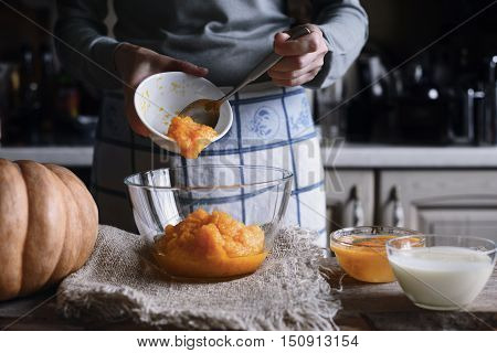 Putting pumpkin puree in the glass bowl horizontal