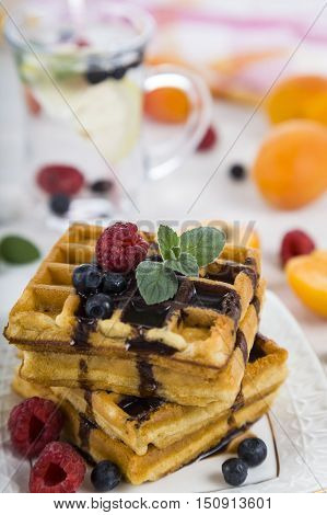 Delicious waffle with berries and chocolate on wooden table