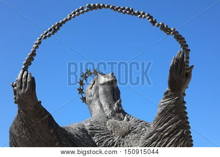Lisbon, Portugal - July 28, 2016:  Statue of woman looking at Cristo Rei. Ist located in front of the Cristo Statue in Almada. Lisbon. Portugal