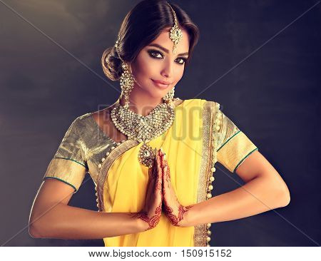 Portrait of beautiful indian girl . Young hindu woman model with tatoo  mehndi and kundan jewelry . Traditional Indian costume yellow saree poster