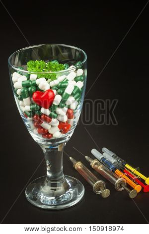 Glass of pills vitamins and syringe. Drugs in a glass container on a black background. Nutritional supplements for athletes. Diet concept. Pharmacological treatment of diseases.