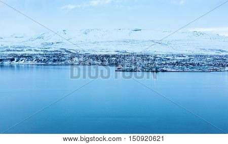 Akureyri, with Hlidarfjall behind, viewed from the eastern shore of Eyjafjordurat dusk in winter, northern Iceland.