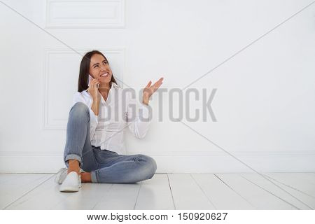 A photo of young woman sitting on the floor and talking on the smart phone. She is wearing denim light-gray skinny jeans and a white fitted blouse