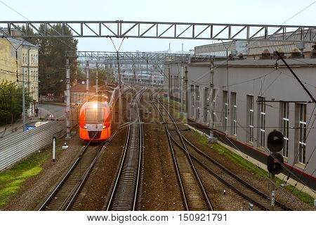 SAINT-PETERSBURG RUSSIA - September 27 2016: modern locomotive pulling a high-speed electric train Lastochka (Swallow) on rails. Technical railway station - operational locomotive depot on autumn morning in fog. Transport infrastructure of Russian Railway
