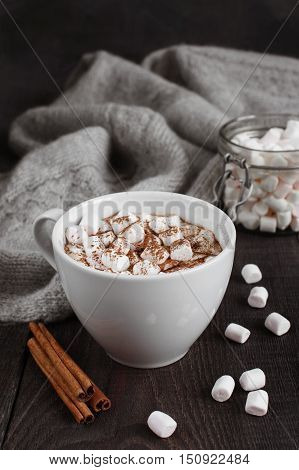 The cap of beverage with marshmallow on the dark wooden table