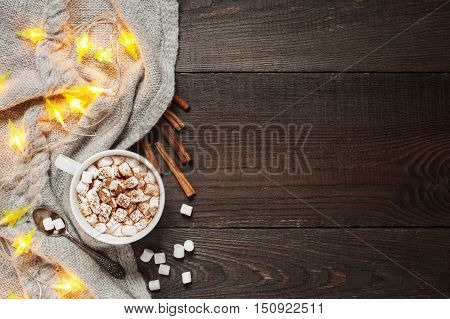 Wooden background with cap of cacao marshmallow and garland