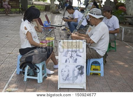 Hanoi, Vietnam - Oct 8, 2016: Asian portrait painter drawing sketch of customer by pencil on the sidewalk of the bank of Hoan Kiem (Sword) lake, Hanoi capital.