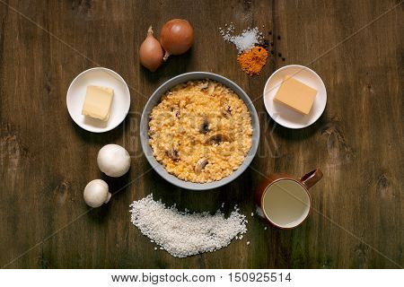 Risotto with mushrooms, fresh herbs and parmesan cheese. Wooden background, top view