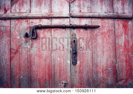 Antique Barn Doors with a rusty bolt. Russian north. Red locked doors with red peeled paint. Kenozersky National Park (UNESCO Biosphere Reserve) Russia.