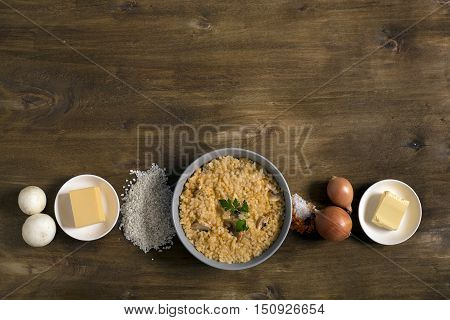 Risotto with mushrooms, fresh herbs and parmesan cheese. Wooden background, top view with copy space
