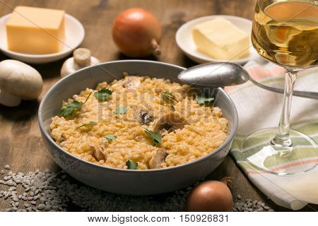 Risotto with mushrooms, fresh herbs and parmesan cheese. Wooden background. Horizontal orientation