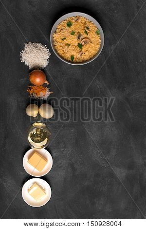 Risotto with mushrooms, fresh herbs and parmesan cheese. black chalkboard, top view vertical orientation