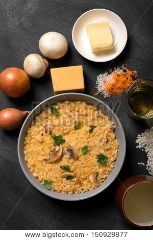 Risotto with mushrooms, fresh herbs and parmesan cheese. black chalkboard, top view