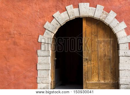 Double door with one side opened - Antique arched entrance with double wooden doors left side opened and the orange-pink wall