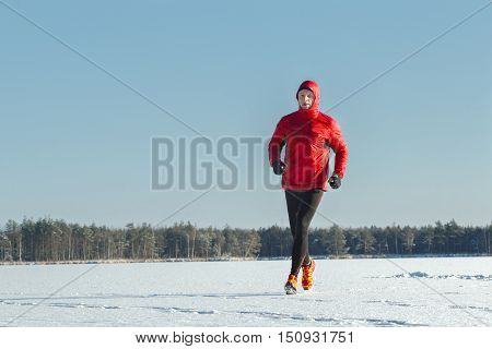 Running man is wearing red protective sportswear on winter training session outdoors