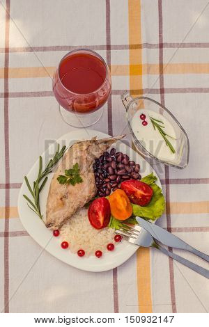 Gourmet roasted rabbit leg with rice and beans. White sauce and glass of tomato juice. Meal is served on white simple plate and checked table cloth, with cutlery. Health and light meal good for diet.