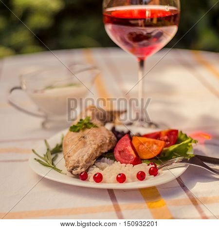 Gourmet roasted rabbit leg with rice and beans. White sauce and glass of red wine. Meal is served on white simply plate and checked table cloth, with cutlery. Health and light meal good for diet.