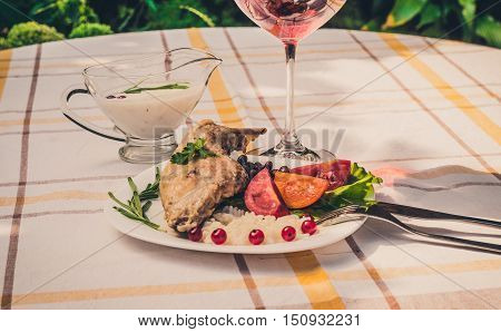 Gourmet roasted rabbit leg with rice and beans. White sauce and glass of red wine. Meal is served on white simple plate and checked table cloth, with cutlery. Health and light meal good for diet.