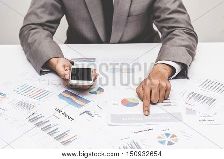 Businessman poiting at business report paper on the table.