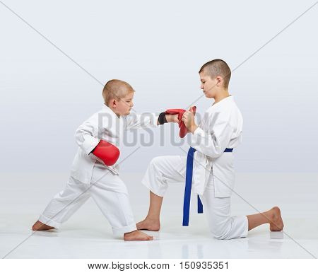 On the simulator little karateka boy is training punch arm