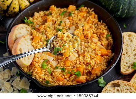 Pumpkin risotto in spoon closeup. iron pan, Parmesan cheese, bread