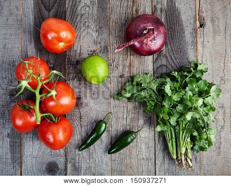 Ingredients for delicious, spicy sauce Pico de Gallo also called salsa Fresca. Traditional recipe, fresh tomatoes, red onion, cilantro, lime juice and spicy jalapenos. National Mexican cuisine.