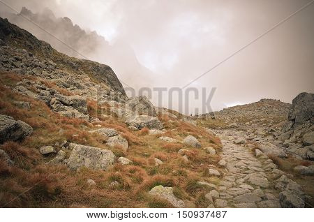 Cloudy mountain landscape. Mountain trail in the clouds in High Tatra Slovakia.