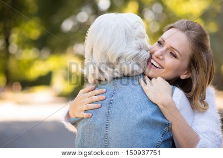 So happy together. Happy and beautiful mother and daughter hugging and smiling while having a walk in the park.