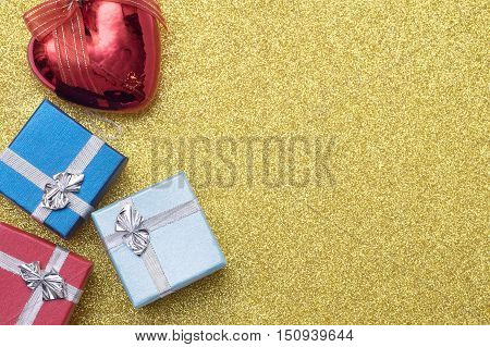 Three Small Box And Christmas Heart Shaped Red Ball On Yellow Background