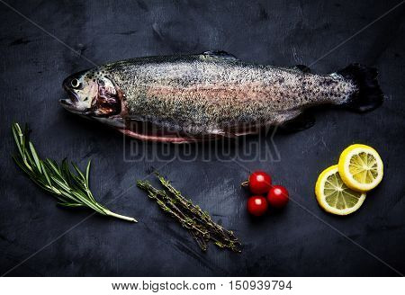 Raw fresh gutted rainbow trout with cherry tomatoes, slices of lemon, sprigs of rosemary and thyme. Preparations for cooking delicious fish on black background. Top view, saturated colors