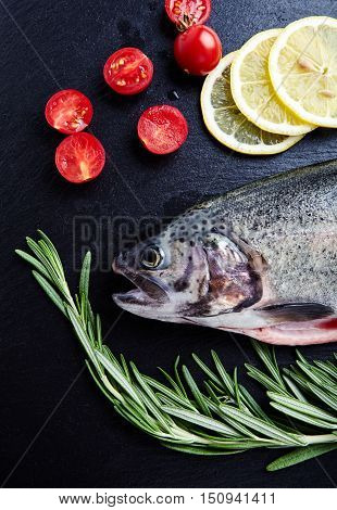 Close up shot of raw fresh rainbow trout on a black background with halved cherry tomatoes, slices of lemon and sprigs of rosemary. Preparations for cooking delicious fish.