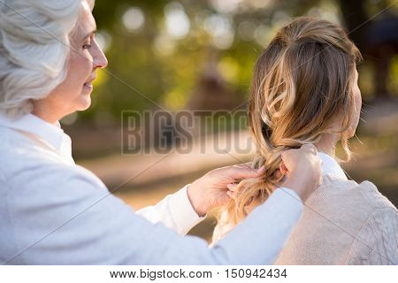 Oh my little daughter. Gray haired pretty woman smiling and plaiting her daughter hair while having a walk.
