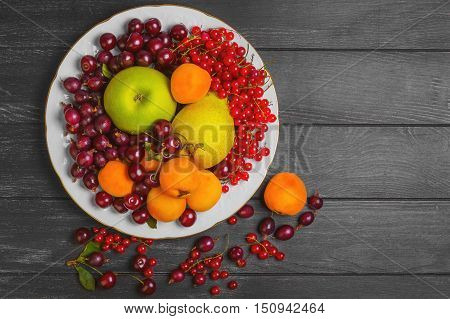 Assortment of fresh fruits and berries. Fruits apricot apple pear. Berries red currants cherries gooseberries. Black wooden table fruit and gooseberries apricots red currants cherries. Top view