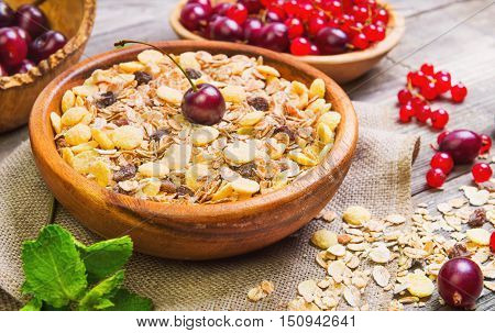 Morning breakfast muesli mix of cereals dried fruits berries in bowl. Fresh red berries to muesli cereals cherries gooseberries redcurrants. Muesli cereals berries scattered on table.