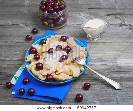 In blue ceramic dish fruit and berry dumplings with cherries. Fresh cherry dumplings for bank. Sour cream for dumplings with cherries. Gray wooden background.