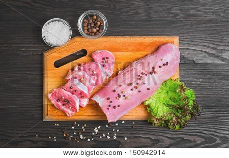 Raw meat pork tenderloin on cutting board ready to cook pork tenderloin cut into pieces of medallions. Seasonings for pork tenderloin fresh lettuce pepper salt. Dark brown wooden background. Top view