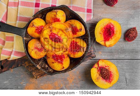 Baked peaches on a cast iron pan leaf cinnamon spices for baked peaches. Fresh red fruit yellow peaches for baking gray wooden background board. Top view.